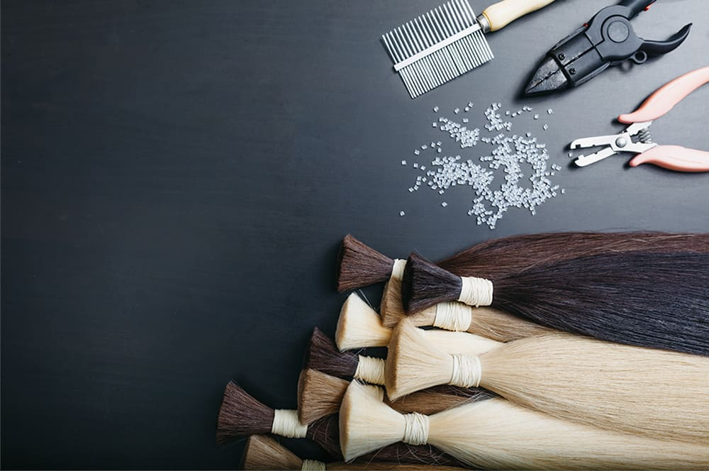 Professional hair extensions equipment, practice hair and tool displayed black background