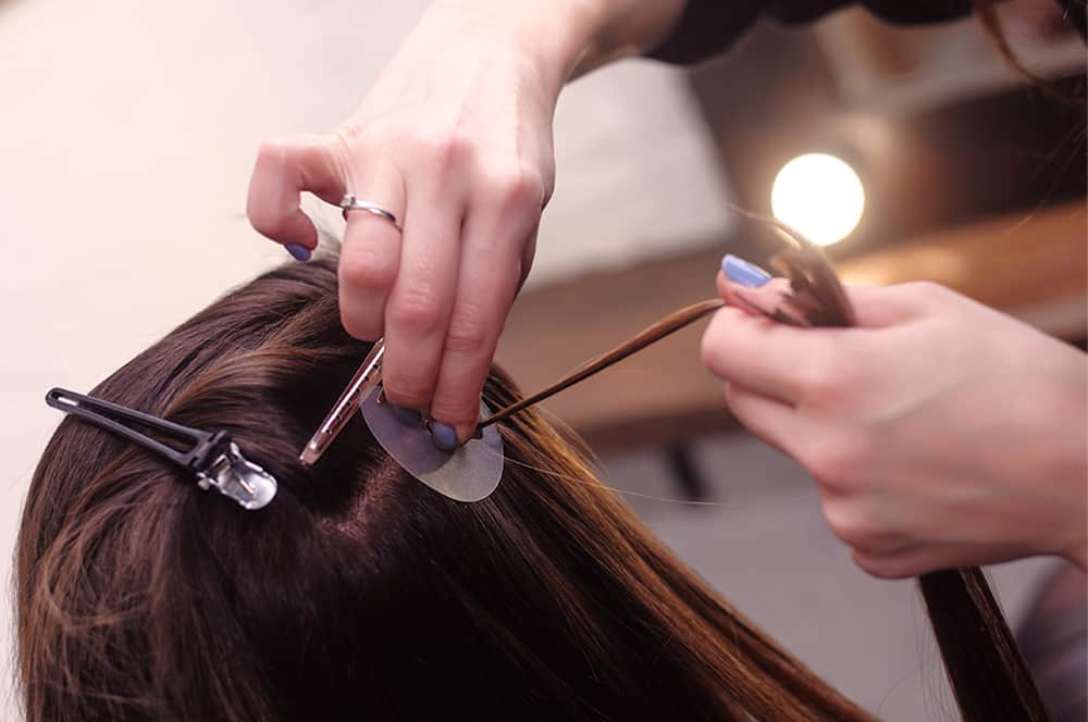 Student training and applying hair extensions in studio